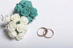 背景钮扣眼上插的花看板卡装饰装饰邀请婚姻白色的珍珠玫瑰 人造花花束和婚戒说谎白色表面上 库存图片