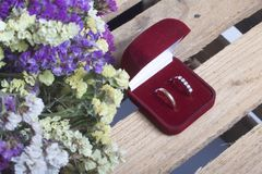 背景钮扣眼上插的花看板卡装饰装饰邀请婚姻白色的珍珠玫瑰 在箱子的婚戒在一个木箱说谎 干花花束附近 免版税库存图片