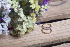 背景钮扣眼上插的花看板卡装饰装饰邀请婚姻白色的珍珠玫瑰 婚戒在一个木箱说谎 干花花束附近 库存照片