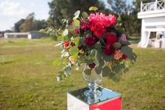 背景钮扣眼上插的花看板卡装饰装饰邀请婚姻白色的珍珠玫瑰 室外婚礼的注册 与红色花的豪华花束 库存图片