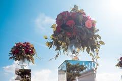 背景钮扣眼上插的花看板卡装饰装饰邀请婚姻白色的珍珠玫瑰 室外婚礼的注册 与红色花的豪华花束 免版税库存图片