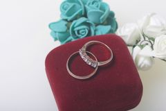背景钮扣眼上插的花看板卡装饰装饰邀请婚姻白色的珍珠玫瑰 白色表面上的婚戒谎言 人造花近的花束  免版税图库摄影
