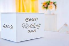 背景钮扣眼上插的花看板卡装饰装饰邀请婚姻白色的珍珠玫瑰 给的金钱白色美丽的箱子 图库摄影