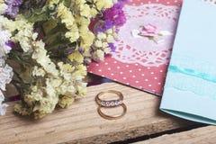 背景钮扣眼上插的花看板卡装饰装饰邀请婚姻白色的珍珠玫瑰 邀请卡片和婚戒,在一个木箱的谎言 干花花束附近 图库摄影