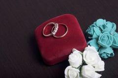 背景钮扣眼上插的花看板卡装饰装饰邀请婚姻白色的珍珠玫瑰 黑暗的表面上的婚戒谎言 人造花近的花束  库存照片