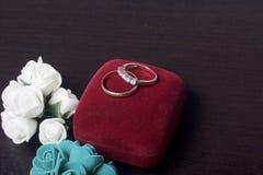 背景钮扣眼上插的花看板卡装饰装饰邀请婚姻白色的珍珠玫瑰 黑暗的表面上的婚戒谎言 人造花近的花束  库存图片