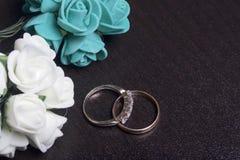 背景钮扣眼上插的花看板卡装饰装饰邀请婚姻白色的珍珠玫瑰 黑暗的表面上的婚戒谎言 人造花近的花束  免版税库存图片
