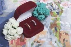 背景钮扣眼上插的花看板卡装饰装饰邀请婚姻白色的珍珠玫瑰 人造花花束和在箱子的婚戒在帆布说谎 库存照片