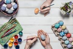 背景面包软绵绵地结块复活节彩蛋酥皮点心准备影子白色 人的手绘与刷子的在老白色木背景的复活节彩蛋和油漆 顶视图 平的la 免版税图库摄影