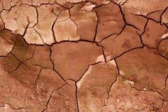 背景黏土崩裂的干红色土壤纹理 库存图片