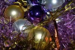 背景,明亮的紫罗兰,银色圣诞装饰,明亮闪亮金属片和金黄 库存图片