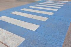 背景:行人交叉路,那个人用途安全地穿过路,不乘汽车,条纹白色和蓝色撞 免版税图库摄影