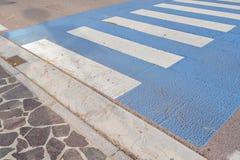 背景:行人交叉路,那个人用途安全地穿过路,不乘汽车,条纹白色和蓝色撞 图库摄影