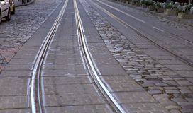 背景 一条老街道的图象有灰色石头铺的路和金属路轨 库存照片