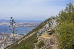 背景直布罗陀、一个被放弃的军用电池、气象台和城市岩石的上面的风景视图  免版税库存图片