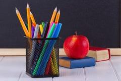 背景黑板白垩、书、铅笔和苹果 库存照片