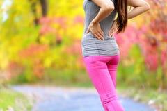 背部疼痛-跑的妇女以背部受伤 免版税库存照片
