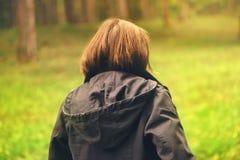 背面图偶然女性走在秋天公园 免版税库存照片