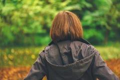 背面图偶然女性走在秋天公园 库存照片