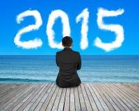 背面图商人坐与2015朵云彩的木地板 免版税库存图片
