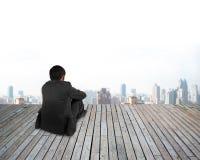 背面图商人递拿着坐与都市的膝盖scen 库存照片