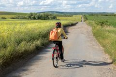 背面图妇女在自行车的骑自行车者乘驾在土路 免版税库存照片