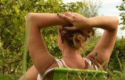 背面图少妇休息的坐一把椅子在庭院里和握在她的头后的手 免版税图库摄影