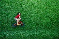 背面图愉快的亚洲孩子 自行车的女孩在绿色草坪放下在夏日 免版税库存图片