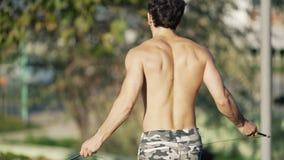 背面图慢镜头,伪装裤子跃迁的运动员与在运动场的一跳绳 肌肉人温暖 影视素材