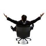 背面图的商人坐椅子和开放胳膊 免版税库存图片