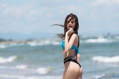 背面图穿戴比基尼泳装的亭亭玉立的女孩和走在沙滩 库存照片