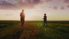 背面图:妈妈和女儿在一个美丽如画的地方跑在日落 活跃生活方式和健康家庭 4k慢动作 影视素材