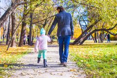 背面图年轻父亲和小女孩走 免版税库存图片