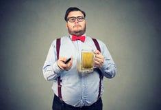 胖的人用遥远的啤酒和的电视 库存图片
