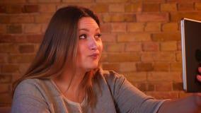 胖的女性模型特写镜头画象微笑地谈话在片剂的videochat在舒适家庭环境 影视素材