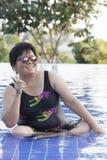 胖的妇女佩带的游泳衣和佩带的太阳镜与 库存照片