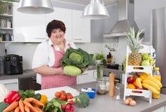 胖的微笑的妇女在做饮食的厨房里 免版税库存图片