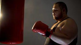 胖的运动员拳击沙袋,体育训练计划,健康活动 免版税库存照片