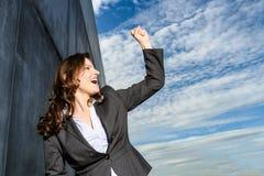胜利姿势的年轻女商人在蓝色多云天空前面 库存照片