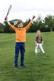 胜利的孩子拿着羽毛球拍和,当站立的兄弟姐妹后边时 图库摄影