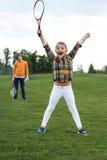 胜利的孩子拿着羽毛球拍和,当站立的兄弟姐妹后边时 免版税库存照片