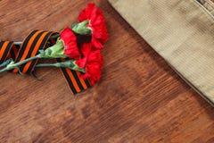 胜利的标志在伟大的爱国战争三个红色花和战士的草料盖帽的在桌上 选择聚焦图象 免版税库存图片