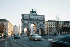 胜利门凯旋门Siegestor在背景中 斋戒在前景的被弄脏的行动汽车 慕尼黑 德国 免版税库存图片
