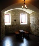 细胞在修道院里 一张桌和两条长凳在有一个拱顶式顶棚和石墙的一间屋子里 免版税图库摄影