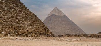 胡夫伟大的Khafre金字塔和金字塔在远的距离的有多云天空背景位于吉萨棉政府,开罗,埃及 库存图片