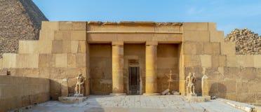 胡夫太平间寺庙胡夫在背景中,吉萨棉,埃及金字塔的吉萨棉金字塔复杂显露的零件的  免版税库存图片