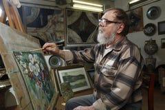 戴胡子和眼镜的年长画家由油漆画花图片在艺术车间 库存照片