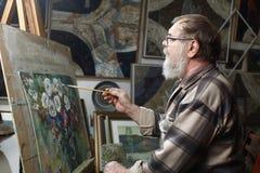 戴胡子和眼镜的年长画家由油漆画花图片在艺术车间 免版税库存图片