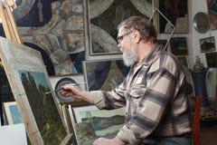 戴胡子和眼镜的年长画家由油漆画花图片在艺术车间 库存图片
