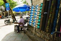 胡志明,越南- 2017年11月20日:老人与在街道的缝纫机一起使用 库存照片